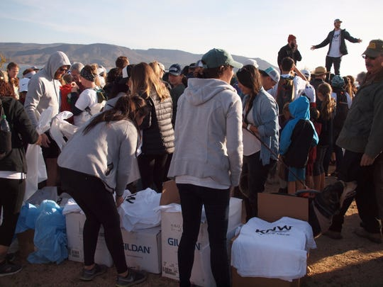 Wild Keepers hand out free volunteer shirts at the beginning of the Impact Friday cleanup on Nov. 23, 2018.