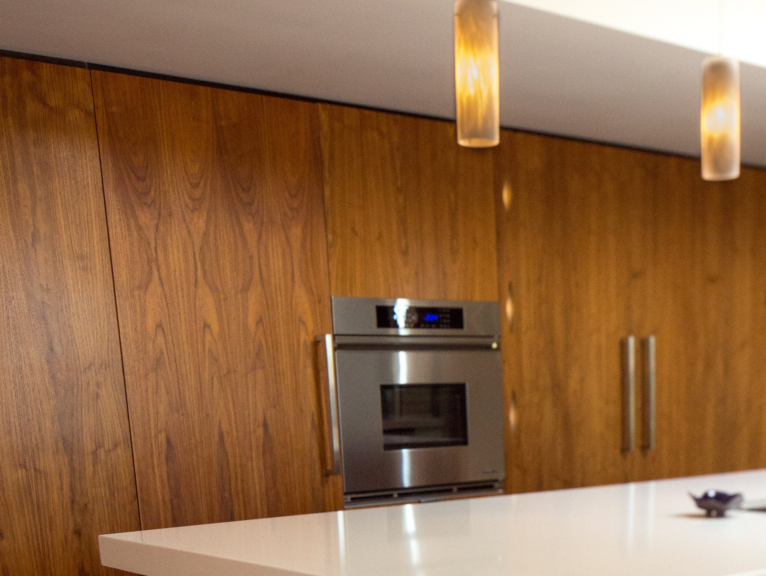 In the kitchen, walnut veneer provides a clean surface while concealing the refrigerator, pantry, dish storage, liquor cabinet – and the door that leads to the basement-turned-movie theater.