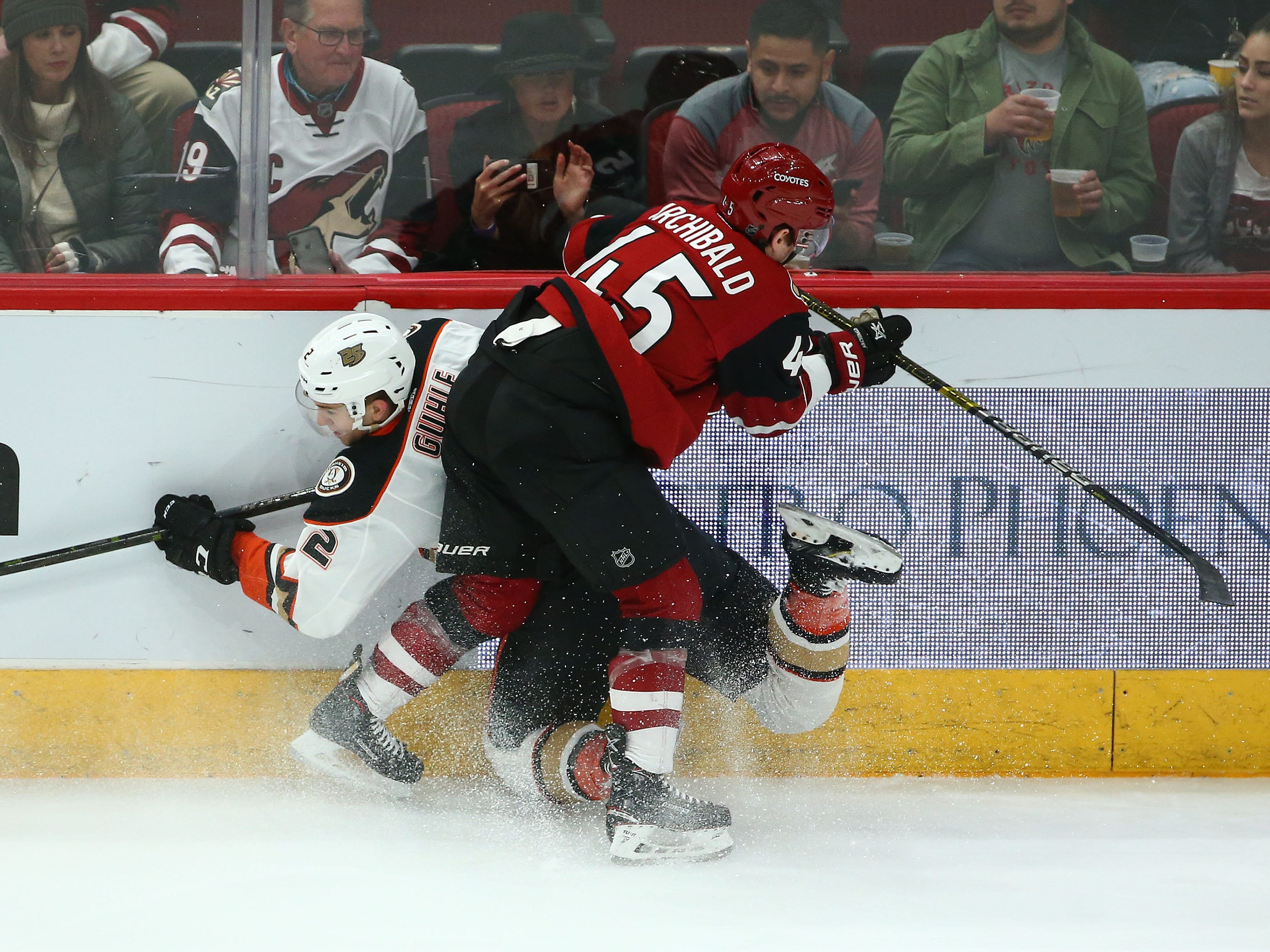Anaheim Ducks defenseman Brendan Guhle (2) is checked into the board by Arizona Coyotes right wing Josh Archibald (45) in the first period on Mar. 5, 2019, at Gila River Arena in Glendale, Ariz.