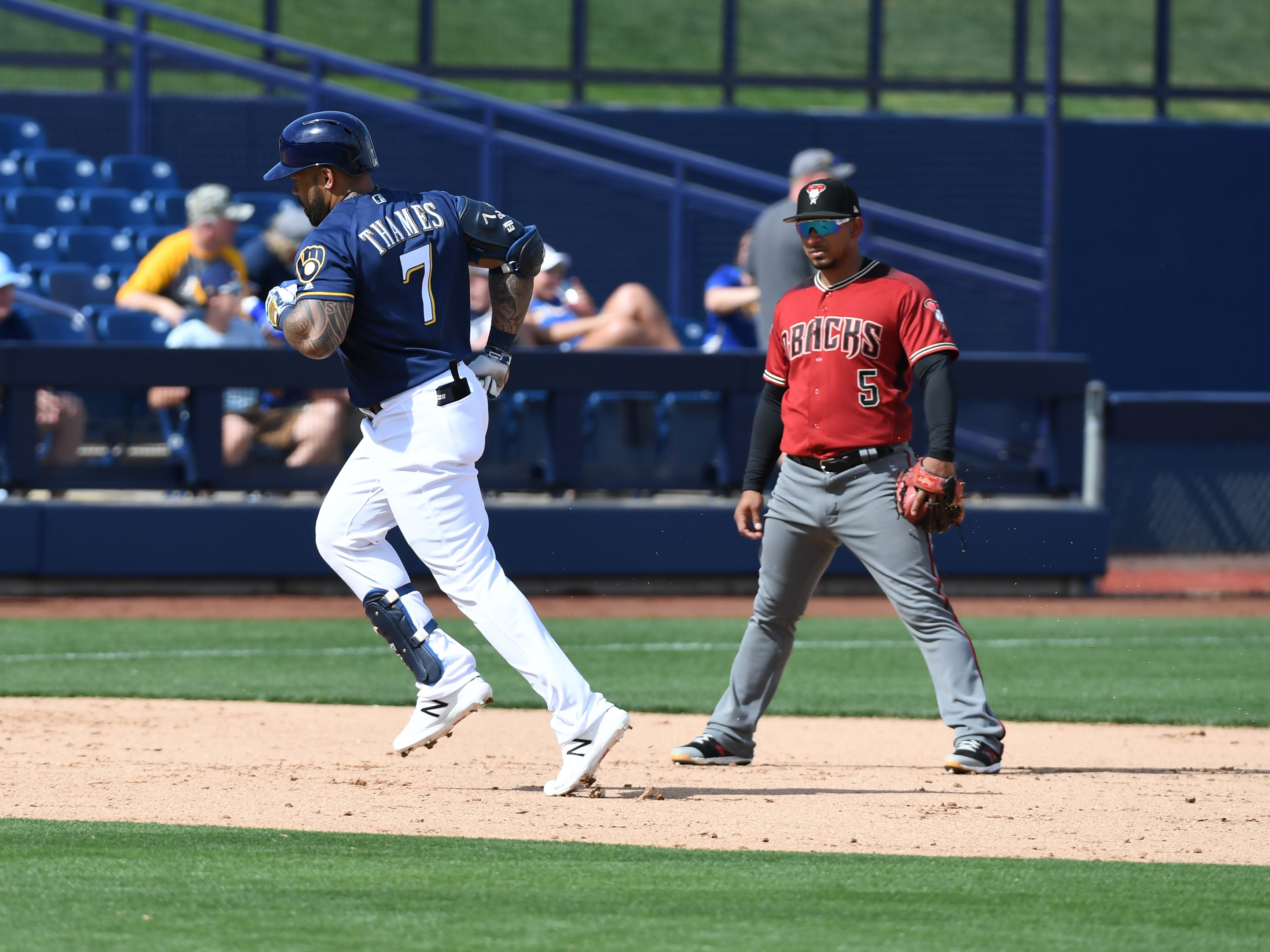 Eric Thames #7 of the Milwaukee Brewers rounds the bases after hitting a home run during the fourth inning of a spring training game as Eduardo Escobar #5 of the Arizona Diamondbacks looks on at Maryvale Baseball Park on March 06, 2019 in Phoenix, Arizona.