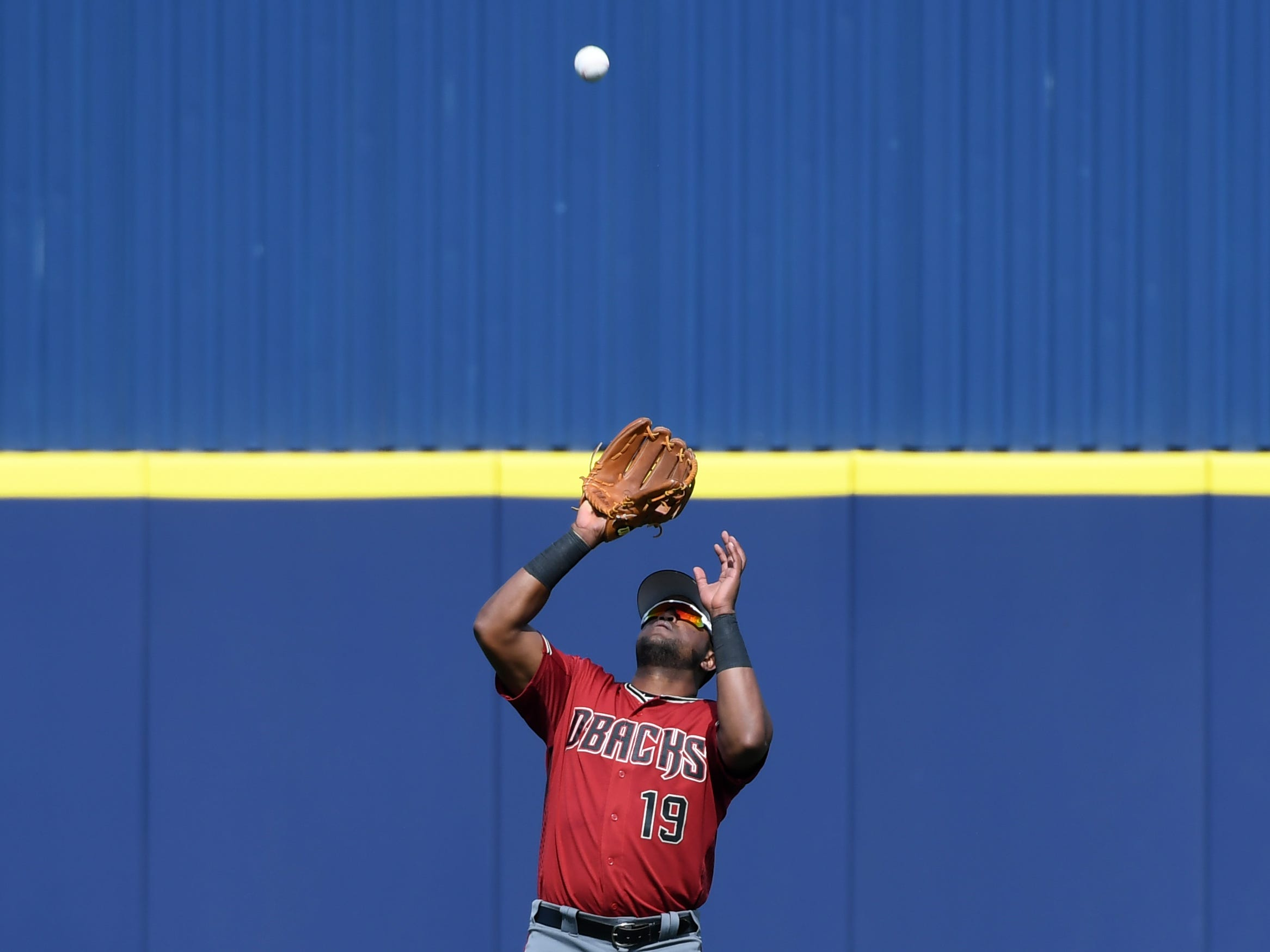 Socrates Brito #19 of the Arizona Diamondbacks catches a fly ball against the Milwaukee Brewers during the fourth inning of a spring training game at Maryvale Baseball Park on March 06, 2019 in Phoenix, Arizona.
