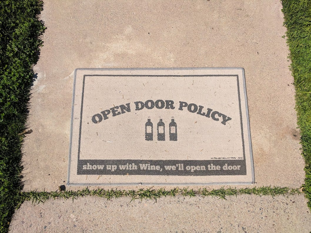 The couple's love of wine, and neighborly visits, extends all the way to the sidewalk with this playful door mat.