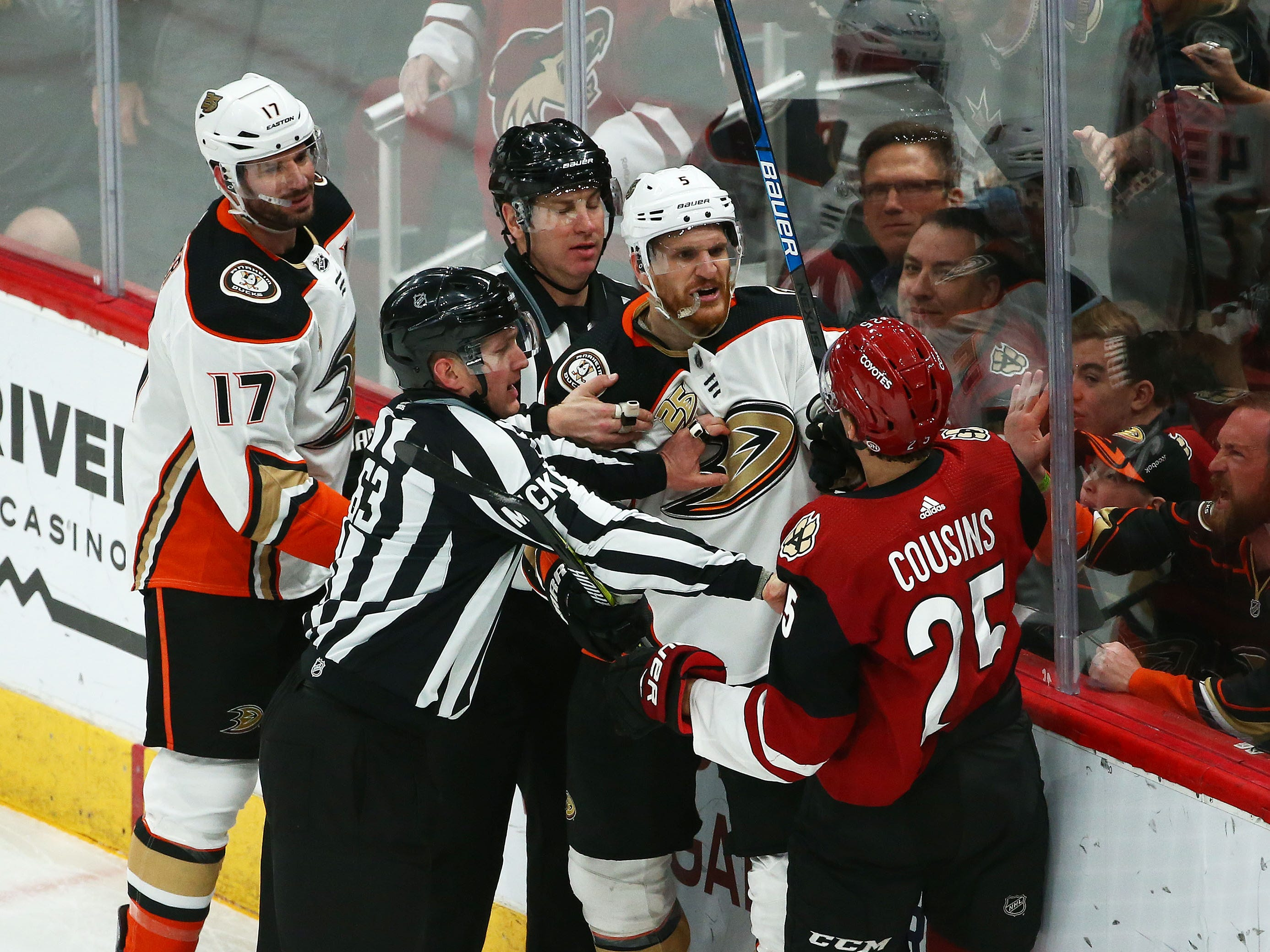 Arizona Coyotes center Nick Cousins (25) and Anaheim Ducks defenseman Korbinian Holzer (5) exchange words in the first period on Mar. 5, 2019, at Gila River Arena in Glendale, Ariz.