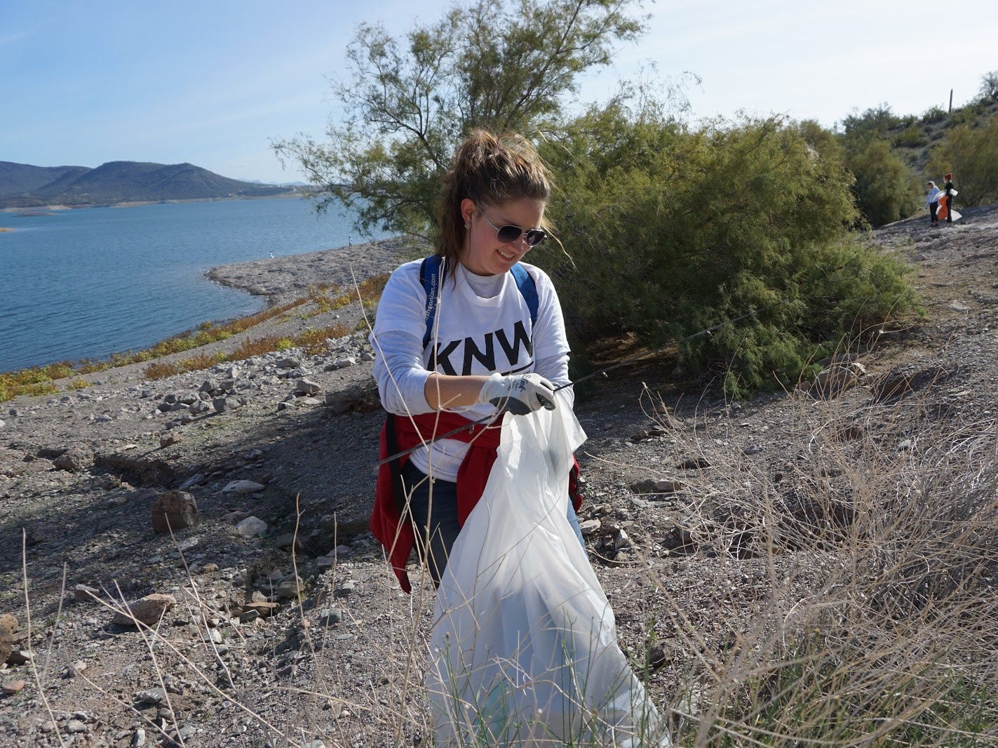 A Keep Nature Wild volunteer wears the free shirt handed out to the first 500 volunteers at a cleanup at Lake Pleasant Park on Nov. 23, 2018.
