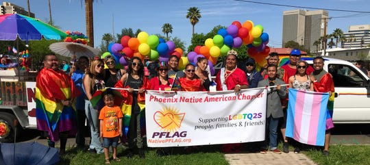 Volunteers from the Native PFLAG chapter in Phoenix pose together during the Phoenix pride parade in 2018.
