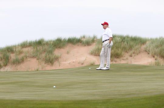 El presidente Donald Trump juega golf en su campo.