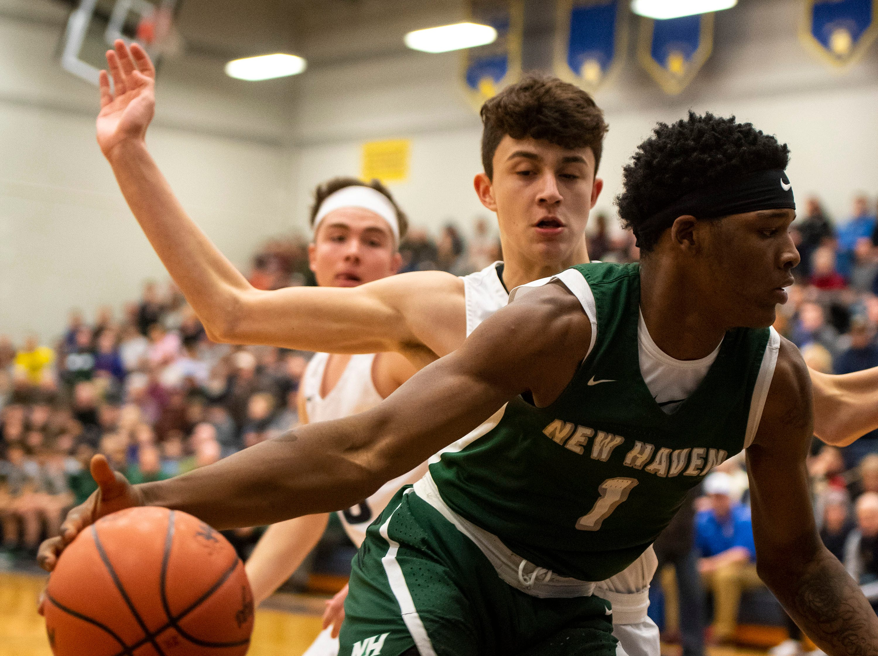 New Haven High School's Romeo Weems (1) pushes around Goodrich's Aiden Rubio in the MHSAA District 2 basketball regionals Tuesday, March 5, 2019 at Imlay City High School.