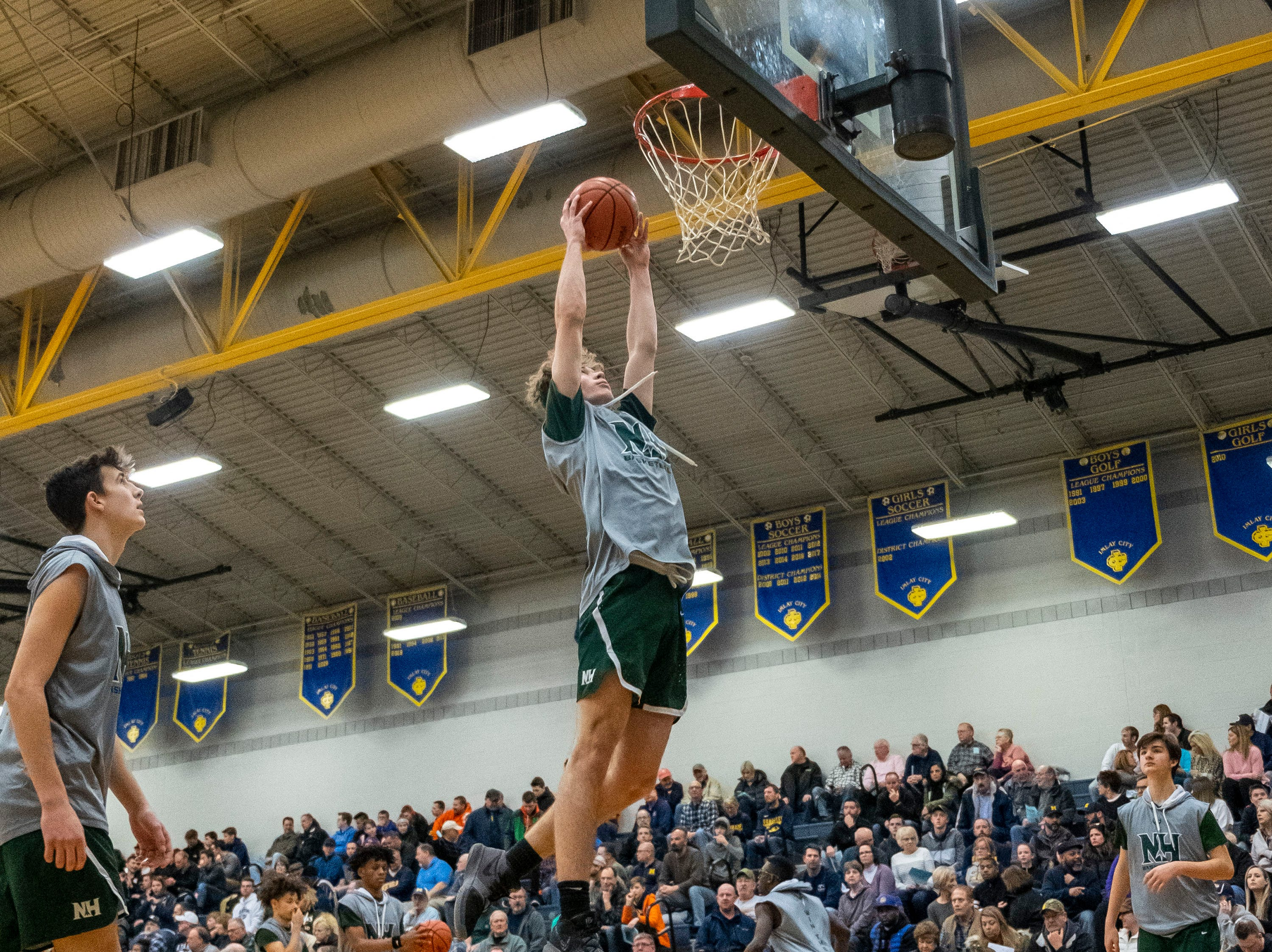 New Haven's Brent Wiles jumps to dunk the ball before taking on Goodrich High School in the MHSAA District 2 basketball regionals Tuesday, March 5, 2019 at Imlay City High School.