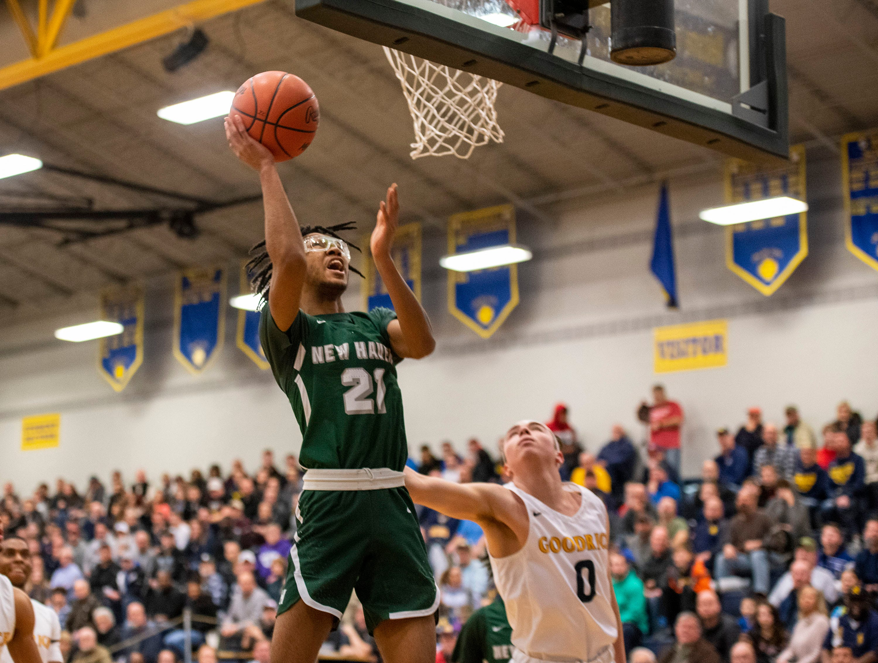 New Haven High School's Jamir Farrior (21) jumps to score in the MHSAA District 2 basketball regionals against Goodrich High School Tuesday, March 5, 2019 at Imlay City High School.