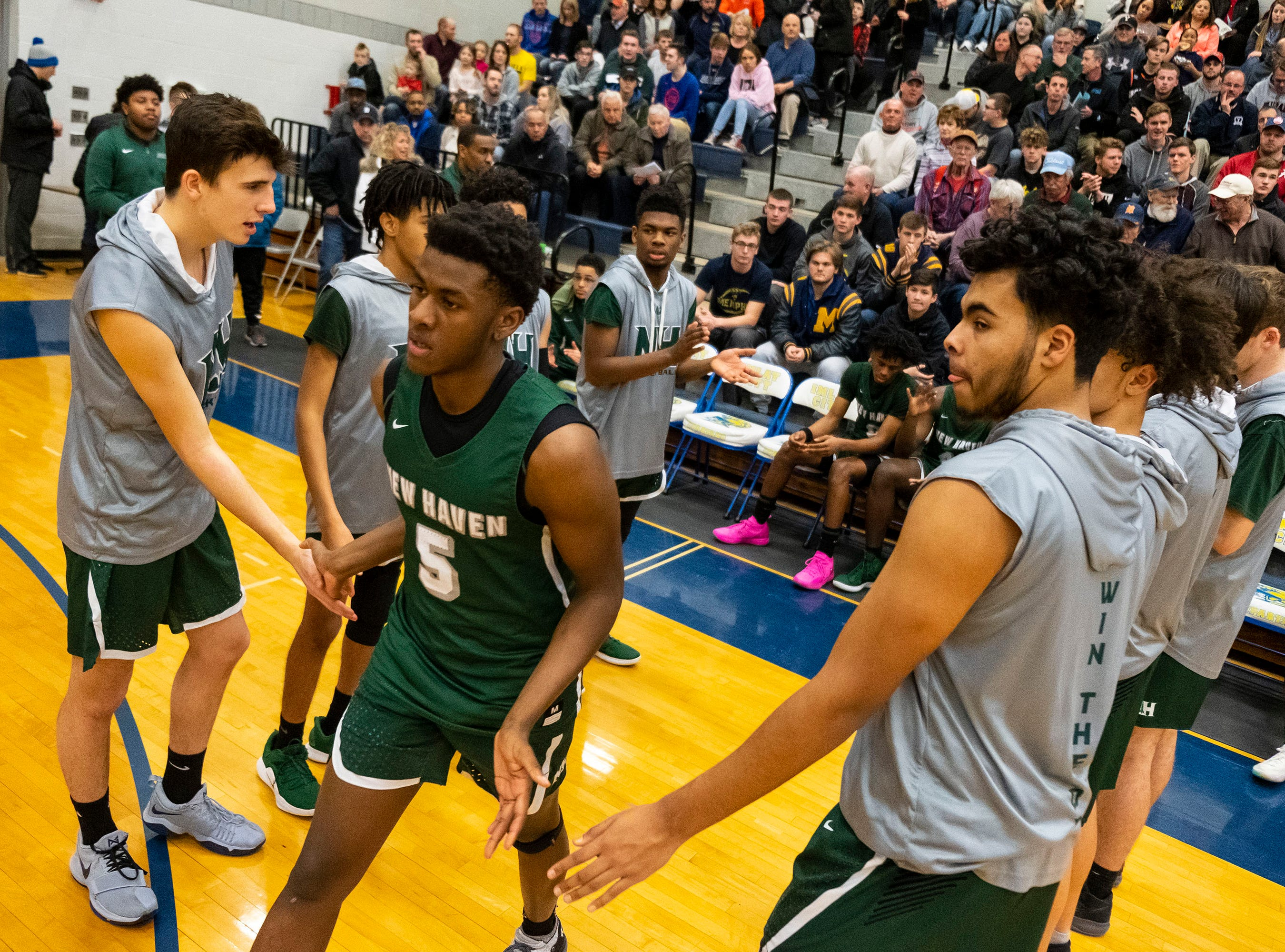 New Haven's Trenell Payne (5) high-fives his teammates at the start of  the MHSAA District 2 basketball regionals against Goodrich High School  Tuesday, March 5, 2019 at Imlay City High School.