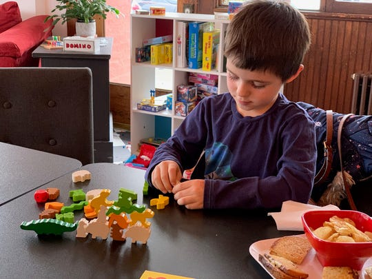 "Alex Milutinovic plays HABA's ""Animal Upon Animal,"" a dexterity game, at the House Rules Cafe in Hudson."