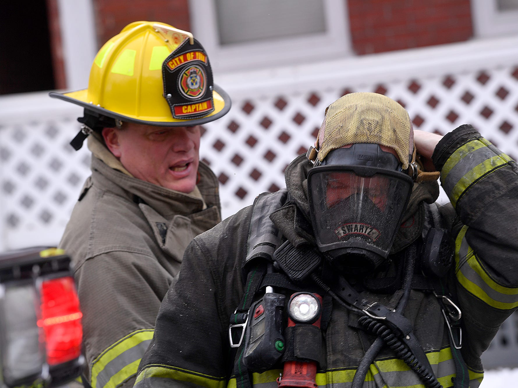York City Fire Captain Kevin Hotzapple helps firefighter Ken Swartz with his air pack after firefighters knocked a blaze in the 200 block of Kurtz Ave., Wednesday, March 6, 2019. One adult and two children were displaced by the blaze.