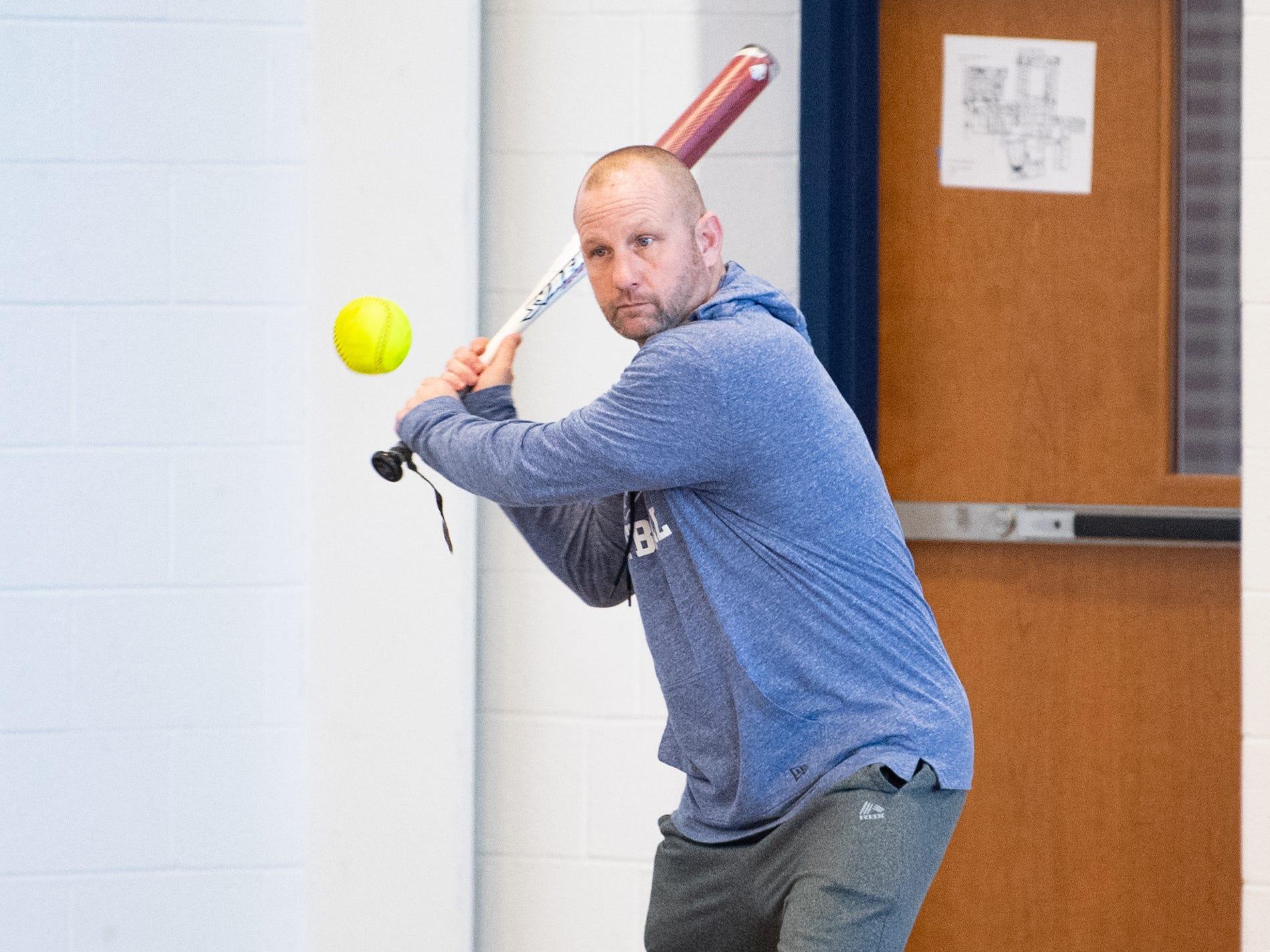 West York's head softball coach tests each baseman by hitting a ball their way, March 5, 2019.