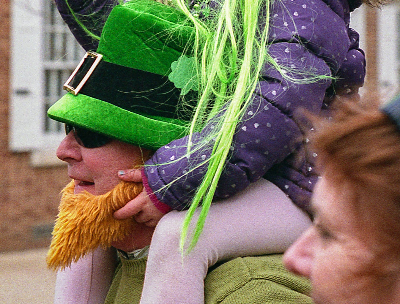 Gentzler likes shooting digitally, but he really enjoys shooting with film more. He loves that that every shot counts. Each time the shutter goes up and down that's one less exposure he can use.  This is a photo of spectators at the 2018 St. Patrick's Day parade. [Nikon F100] [Agfa Vista 200]
