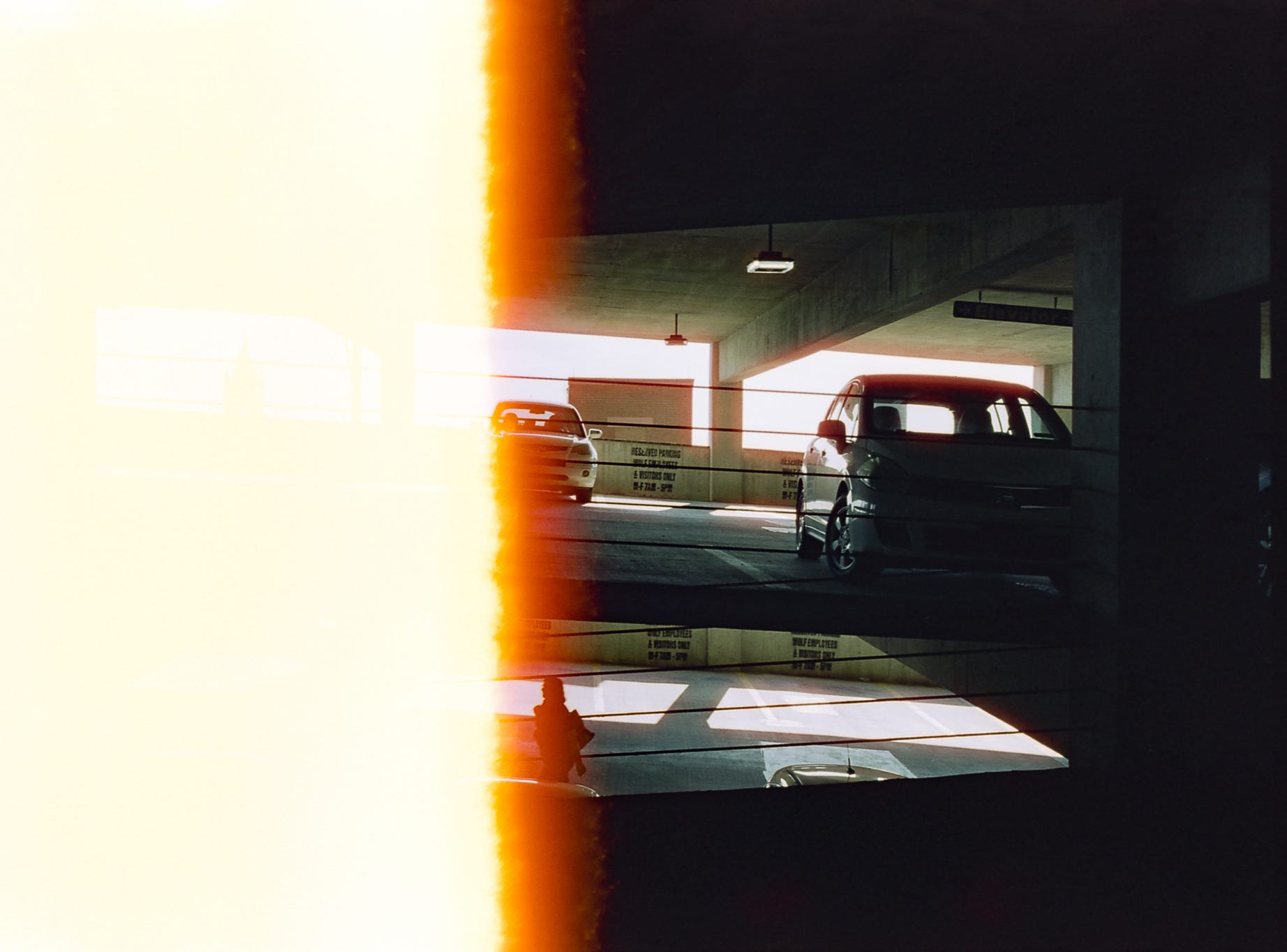 A person walks to their car in the King Street parking garage [Pentax KX] [CineStill 50D]