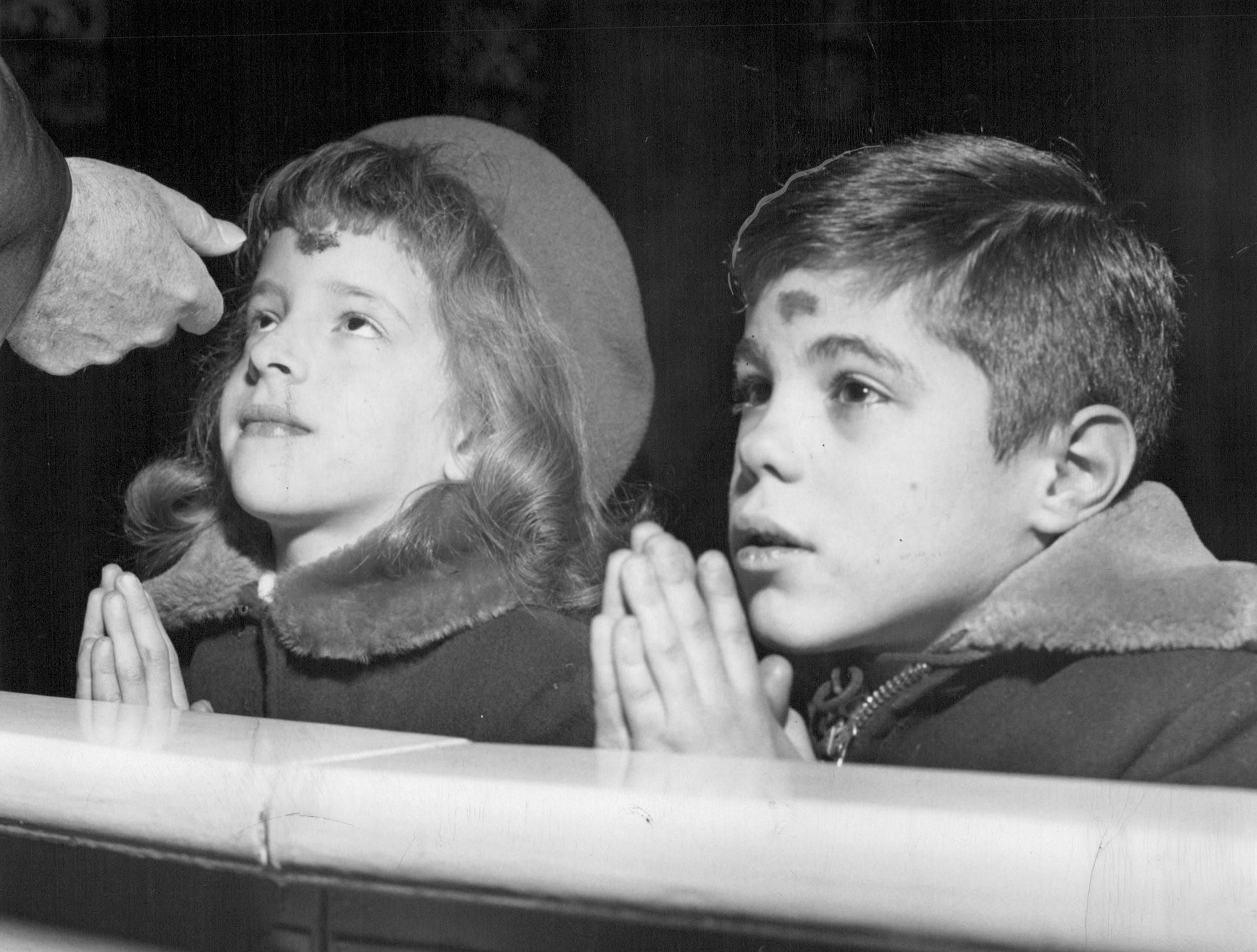 In this photo from 1960, Betsy Auble, 7, and Robert Pesar, 7, kneel to receive cross of ashes on their foreheads from Msgr. Gerald C. Lambert in St. Monica's Church as Ash Wednesday begins Lent.
