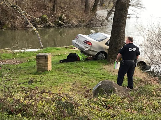 A California Highway Patrol officer watches as a tow-truck driver attaches a cable to a Toyota Corolla that officers say someone dumped in the Sacramento River in Anderson.