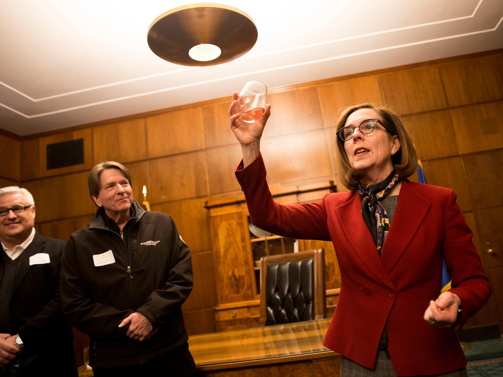 Gov. Kate Brown gives a toast at a release party for the Oregon Solidarity Rose of Pinot Noir as Willamette Valley Vineyard founder and president Jim Bernau and Tim Jennings, of Roth's Fresh Markets look on in the Governor's ceremonial office at the Oregon State Capitol in Salem on Tuesday, March 5, 2019.