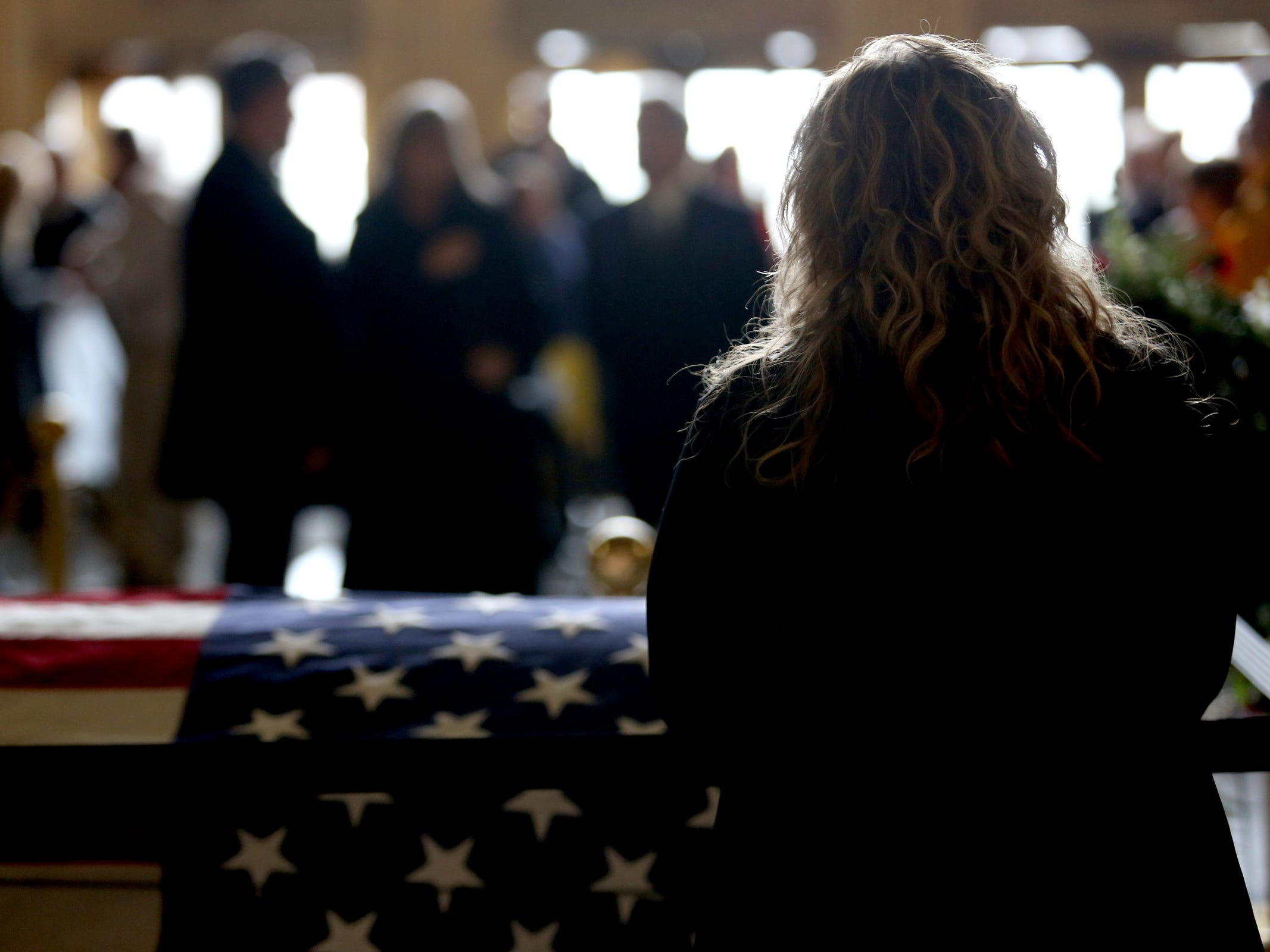 A woman stands near the casket as Secretary of State Dennis Richardson lies in state in the rotunda at the Oregon State Capitol in Salem on Wednesday, March 6, 2019.