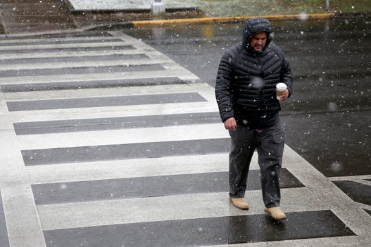 A man crosses State Street as snow falls in Salem on Wednesday, March 6, 2019.