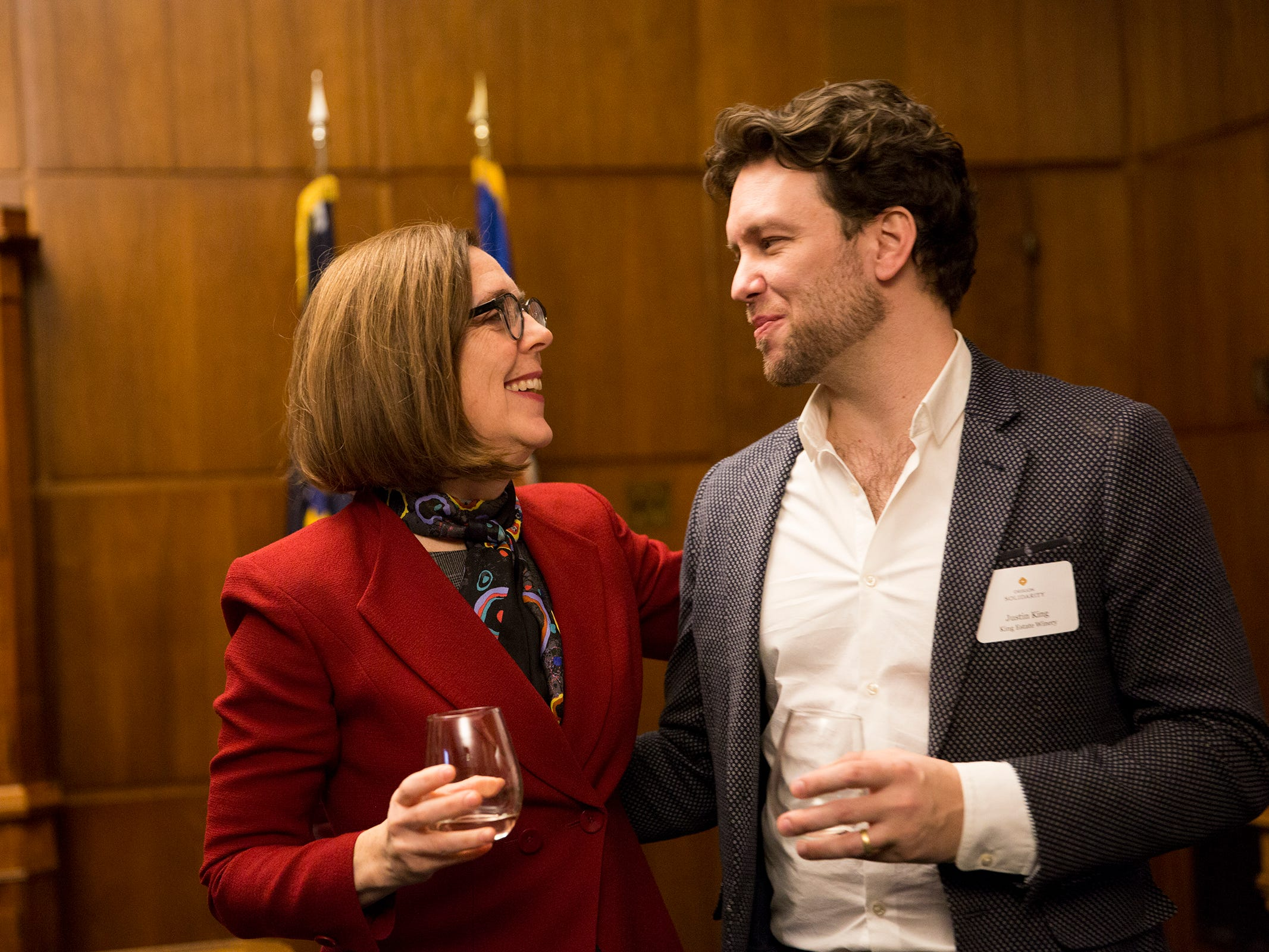 Gov. Kate Brown speaks with Justin King, National Sales Manager for King Estate Winery, at a release party for the Oregon Solidarity Rose of Pinot Noir in the Governor's ceremonial office at the Oregon State Capitol in Salem on Tuesday, March 5, 2019.