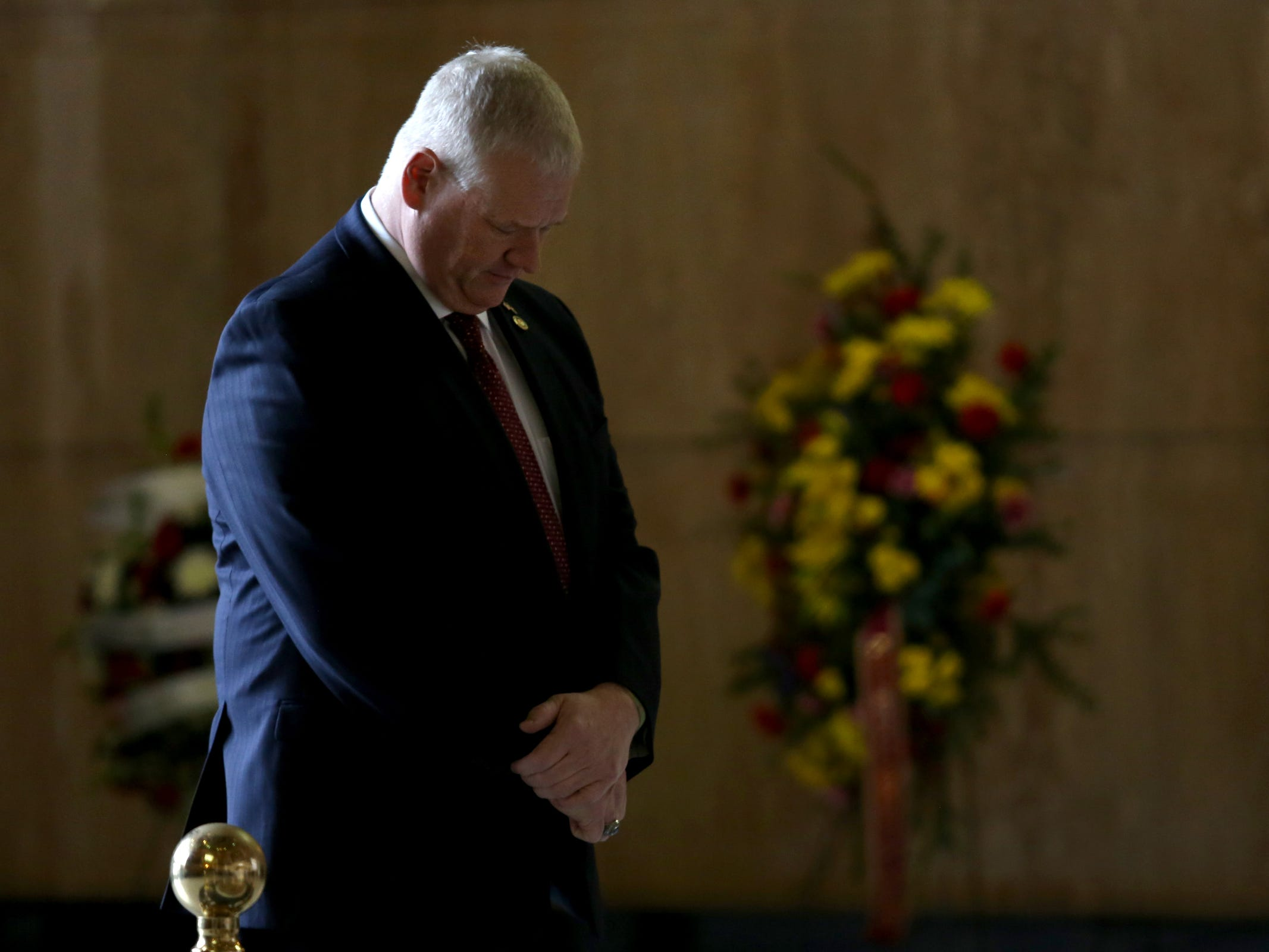 Rep. Paul Evans bows his head as Secretary of State Dennis Richardson lies in state in the rotunda at the Oregon State Capitol in Salem on Wednesday, March 6, 2019.