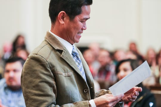 My Ngoc Dang holds his certification as he walks back to his seat during the naturalization ceremony Wednesday March 6, 2019, at the O.C. Fisher Federal Building.