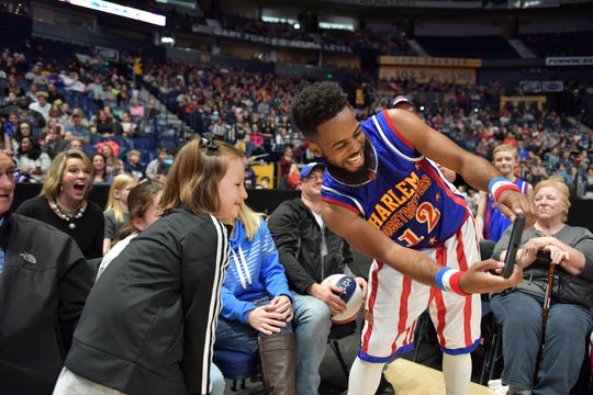 Harlem Globetrotter Ant Atkinson (right) takes a selfie with fans.