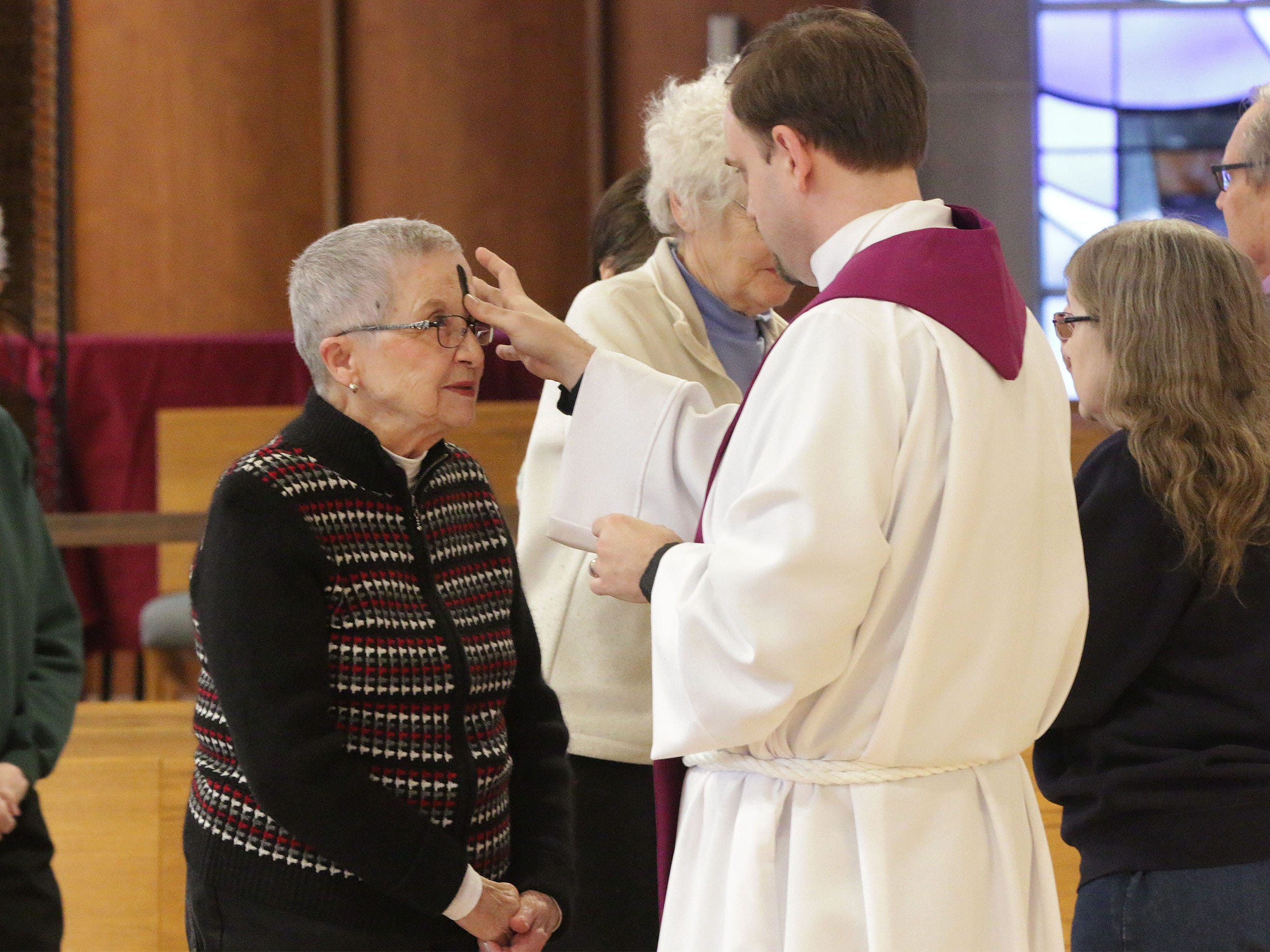 Rev. Matt Hacker, right, places ashes in the sign of the cross on a parishioner during Ash Wednesday service at First United Lutheran Church, Wednesday, March 6, 2019, in Sheboygan, Wis.