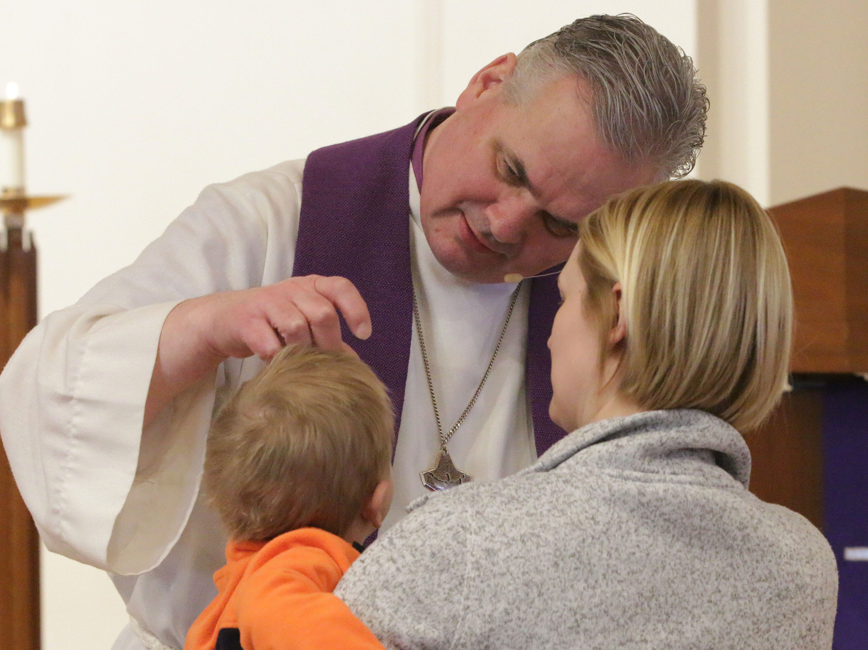 Rev. Todd Smith places ashes on the forehead of Charlie Kolb, 1, while his mom Aimee, both of Sheboygan, holds him during Ash Wednesday service at First United Lutheran Church, Wednesday, March 6, 2019, in Sheboygan, Wis.