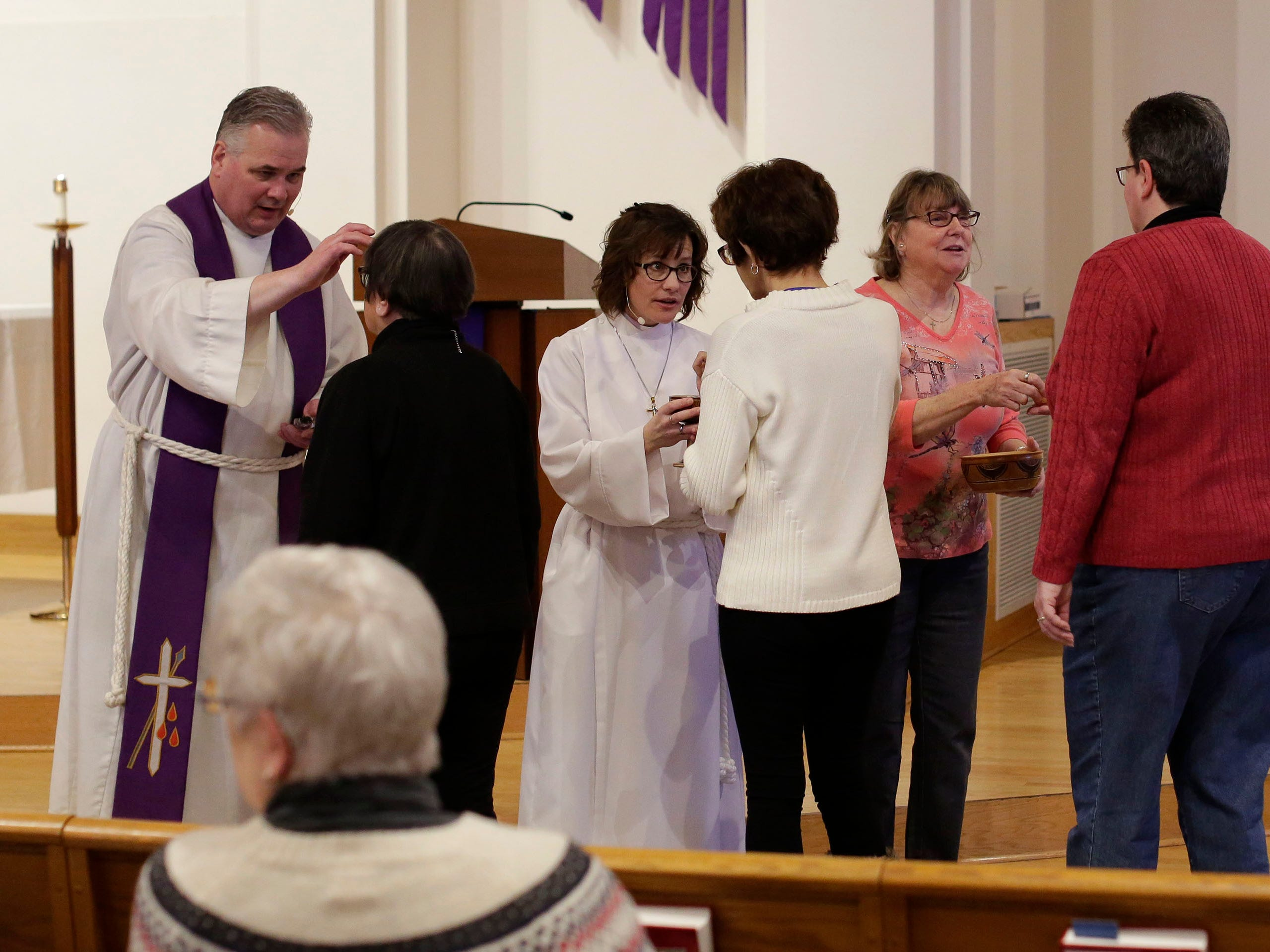 Rev. Todd Smith, left, puts ashes on the forehead of parishioners during Ash Wednesday service at First United Lutheran Church, Wednesday, March 6, 2019, in Sheboygan, Wis.