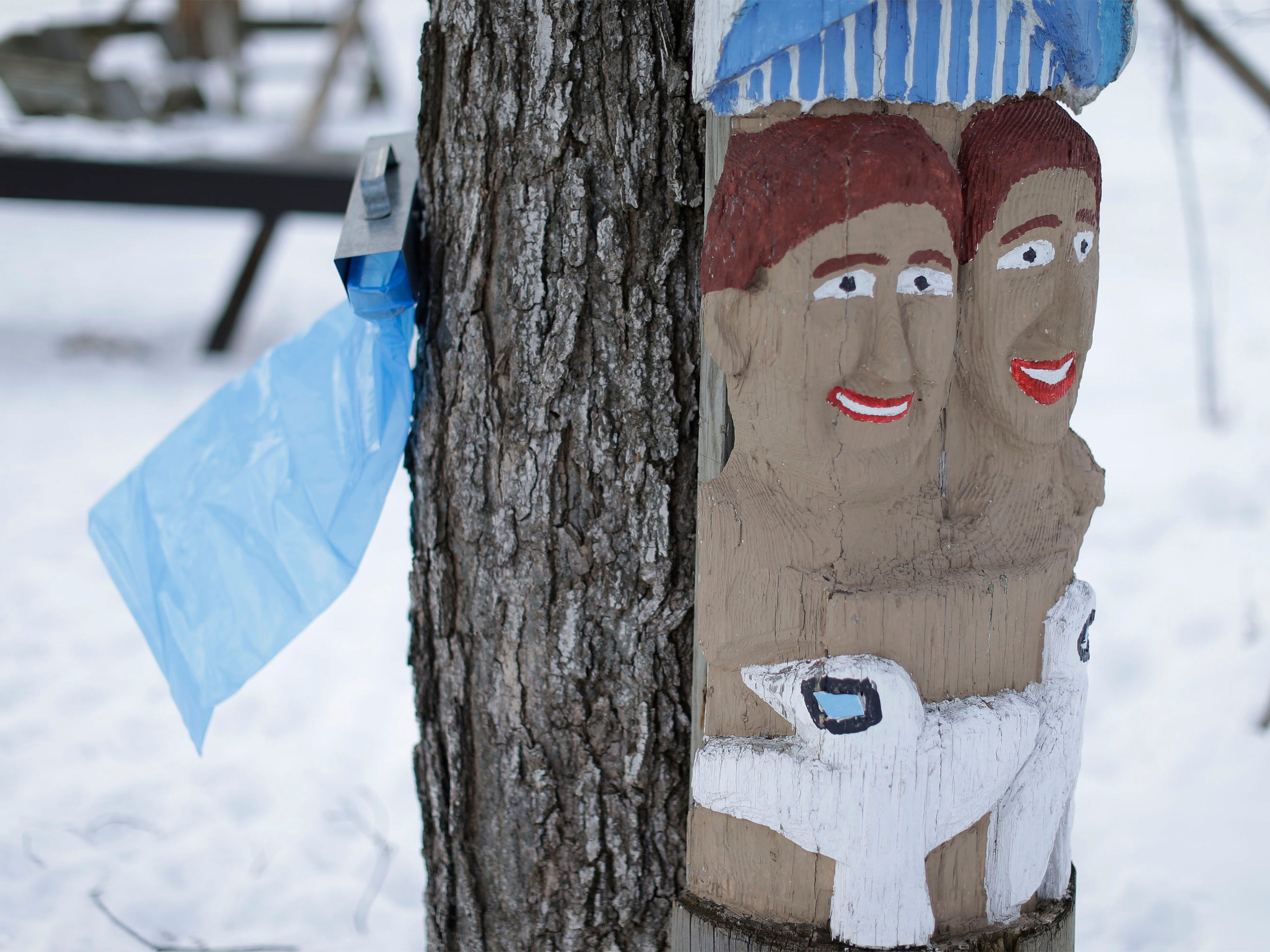 Wind flaps a maple sap bag by a smiling totem pole at the Ellwood H. May Environmental Park, Tuesday, March 5, 2019, in Sheboygan, Wis.