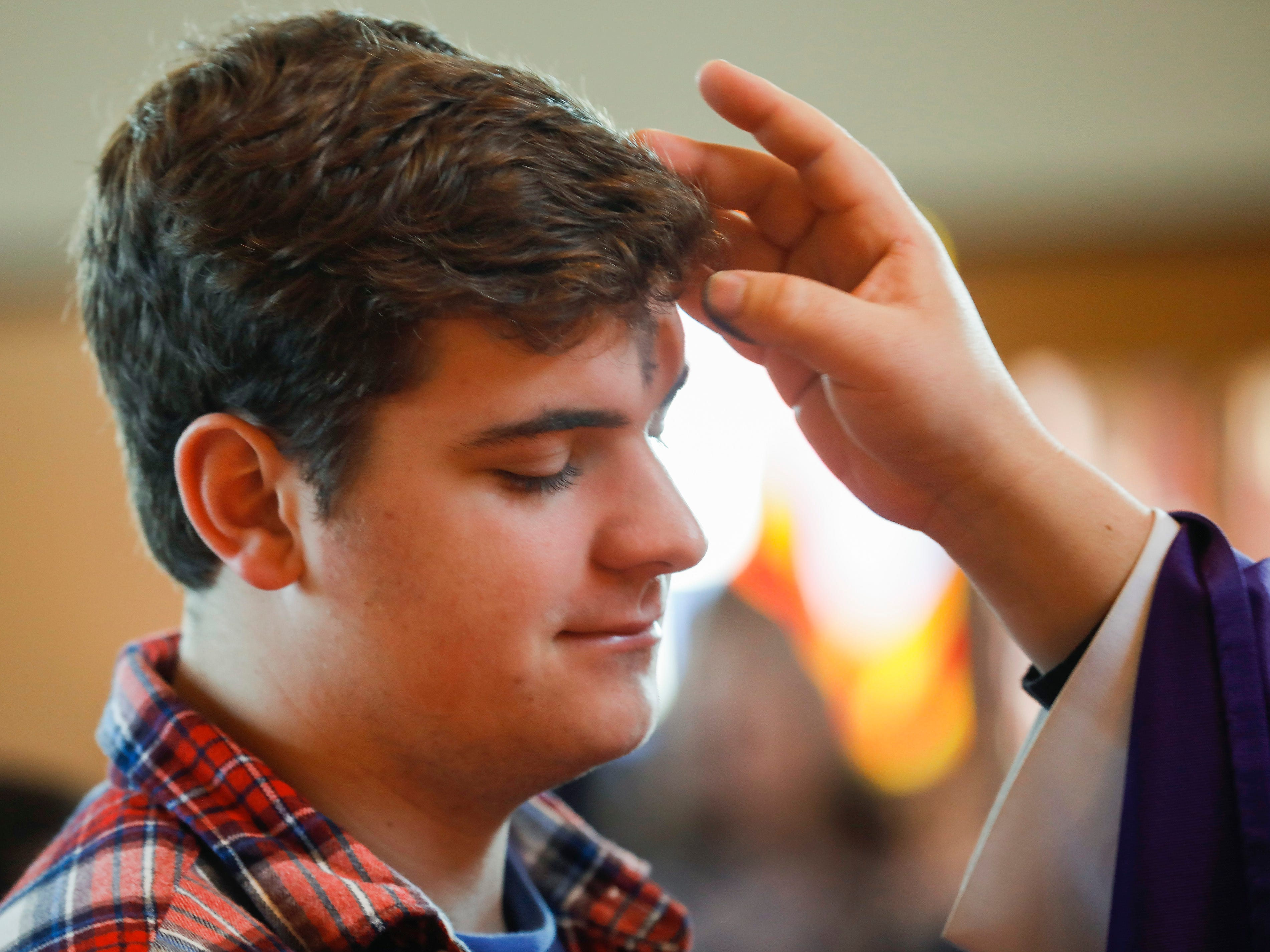 Dominic Masek, a student at Missouri State University, has ashes applied to his forehead during the Ash Wednesday Mass at the Missouri State University Catholic Campus Ministry on Wednesday, March 6, 2019.