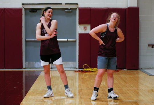 Hayley (left) and Kayley Frank joke with each other during basketball practice on Tuesday, March 5, 2019.