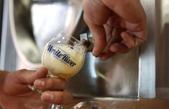 A White River Brewing Company staffer pours a White Creek Wit from a fermentation tank on Tuesday, Oct. 21, 2014.