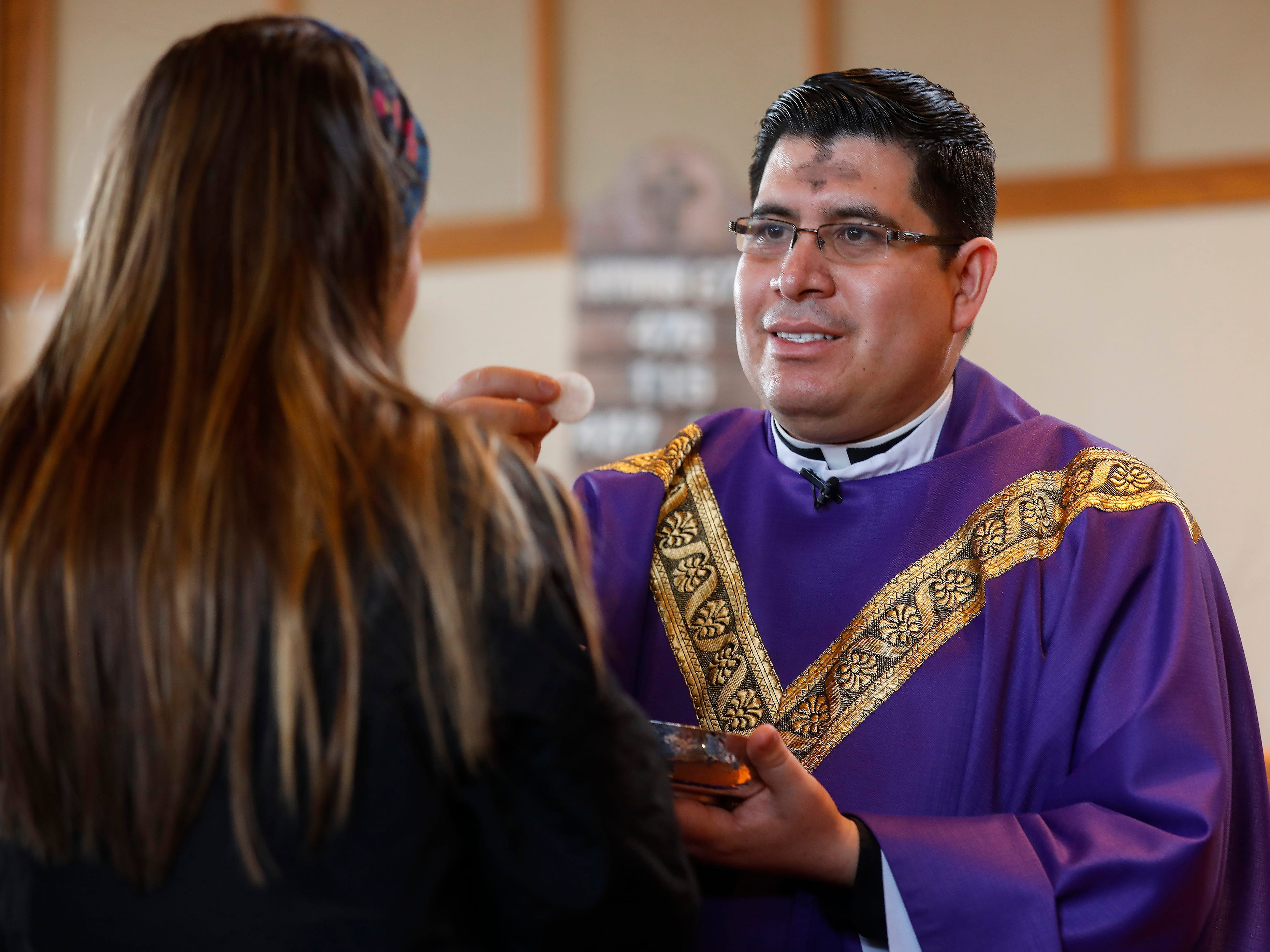 Father Javier Reyes offers the host to a congregant during the Ash Wednesday Mass at the Missouri State University Catholic Campus Ministry on Wednesday, March 6, 2019.