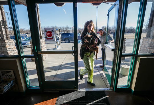 Michael Bartlett holds the door open for Ashlie Alexander, intake coordinator with the Humane Society of Southwest Missouri, as she carries a rescue dog into the building for intake on Tuesday, March 5, 2019.