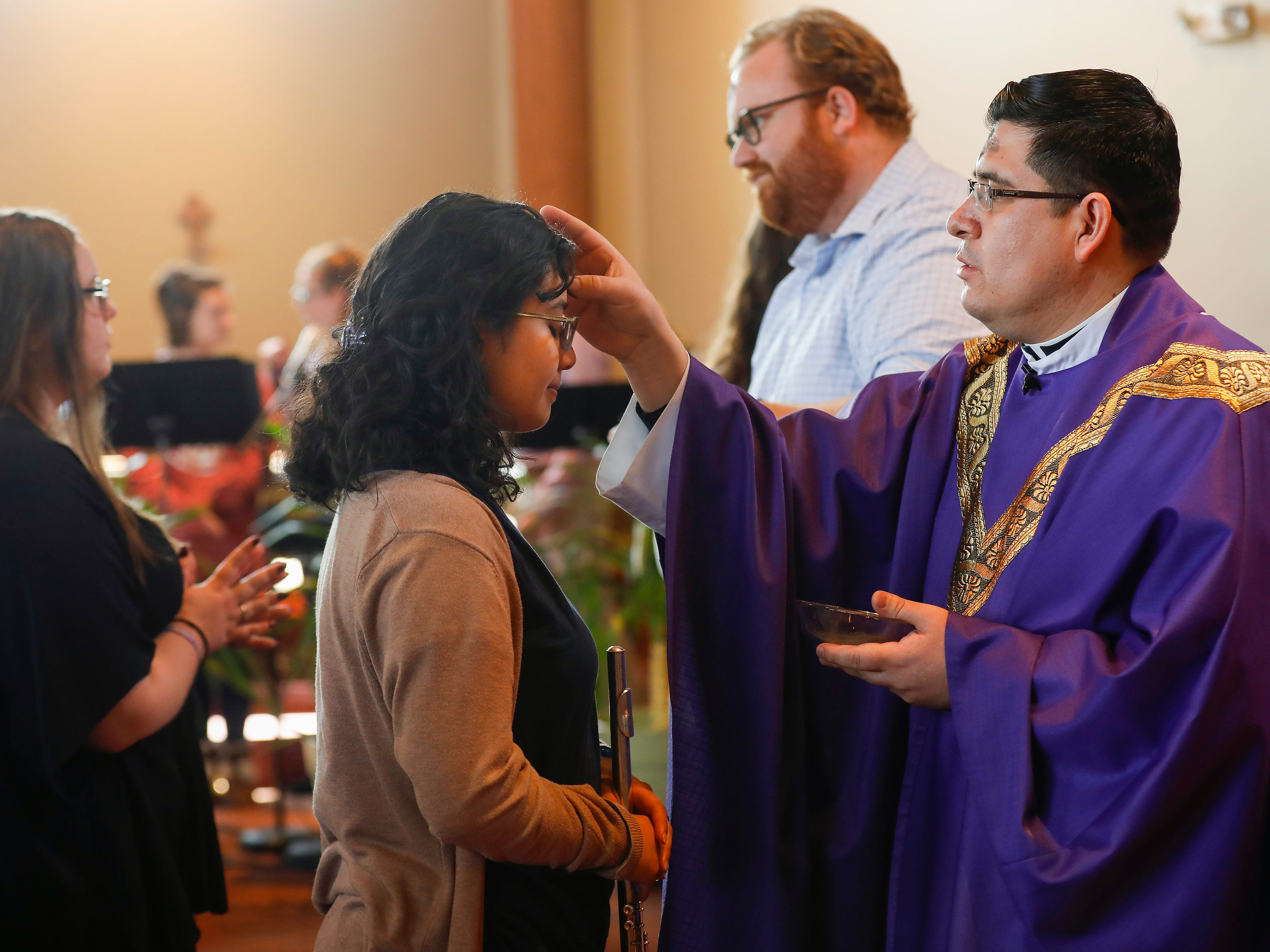 Father Javier Reyes applies ashes to a congregant's forehead during the Ash Wednesday Mass at the Missouri State University Catholic Campus Ministry on Wednesday, March 6, 2019.