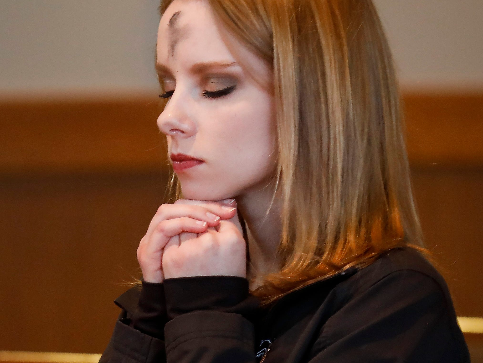 Riley Griesemer, a student at Missouri State University, prays after having ashes applied to her forehead during the Ash Wednesday Mass at the Missouri State University Catholic Campus Ministry on Wednesday, March 6, 2019.