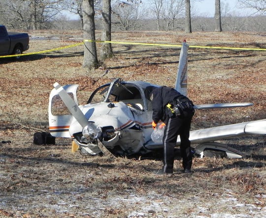 Texas County Sheriff Scott Lindsey gather debris at the scene of a fatal airplane crash Wednesday morning about four miles west of Summersville.