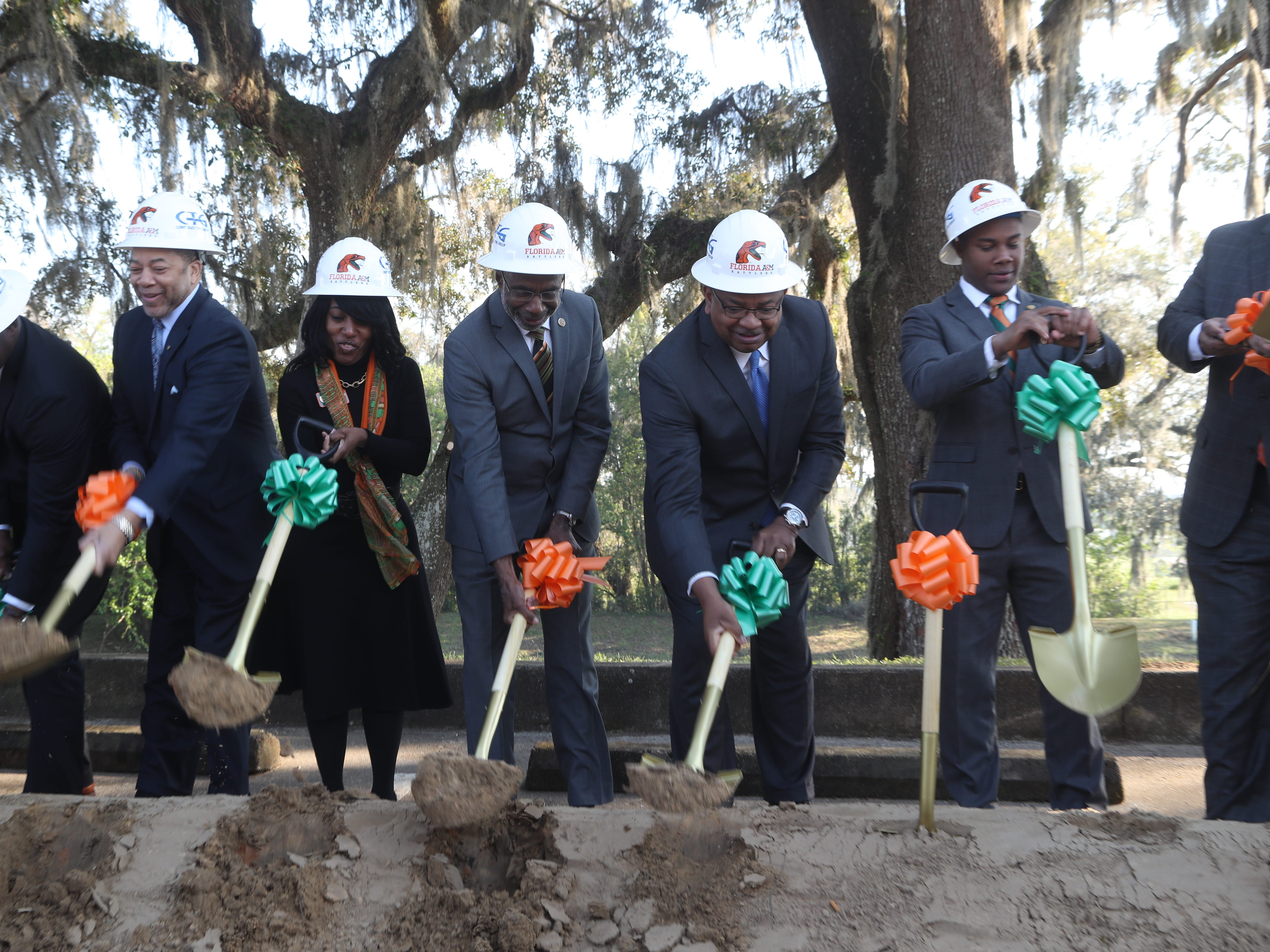 Ceremonial groundbreaking participants dig in during a groundbreaking celebration for a new residence hall on the Florida A&M campus.