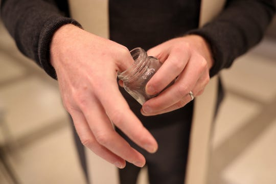 """Rev. David Killeen of St. John's Episcopal Church dips his thumb into a jar of ashes as he waits for the next person who wishes to receive """"ashes to go,"""" an annual practice by Tallahassee Episcopal churches to give out ashes in the Florida Capitol rotunda."""