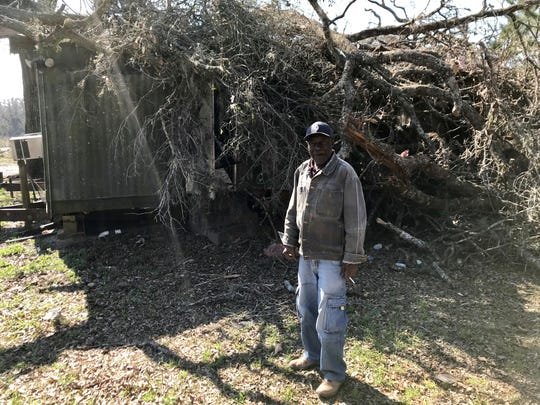 """James """"June Bug"""" Williams stands in the back yard of his Jefferson Road house, which was buried in branches from three different live oaks when a tornado hit March 4, 2019."""