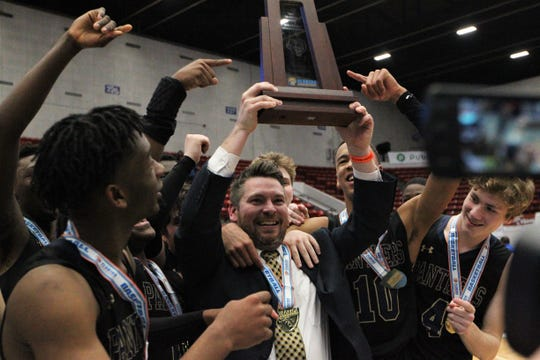 St. John Paul II boys basketball coach Titus Nixon holds the Class 3A state championship trophy after the Panthers beat Orlando Christian Prep 50-48 overtime in overtime at the RP Funding Center in Lakeland on Tuesday.