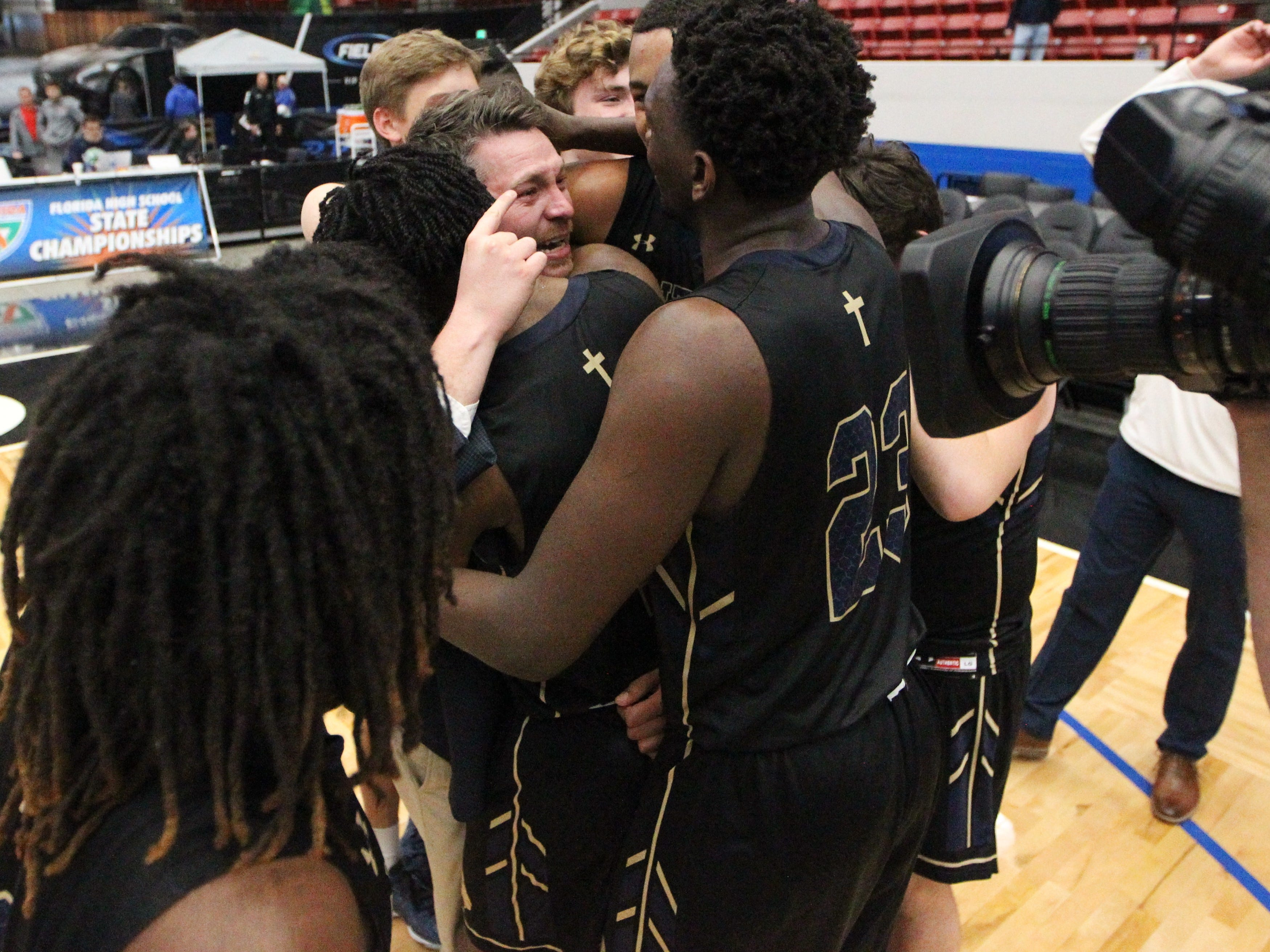 St. John Paul II's as the Panthers' boys basketball team celebrates a 50-48 overtime victory against Orlando Christian Prep to capture a Class 3A state championship at the RP Funding Center in Lakeland on Tuesday.