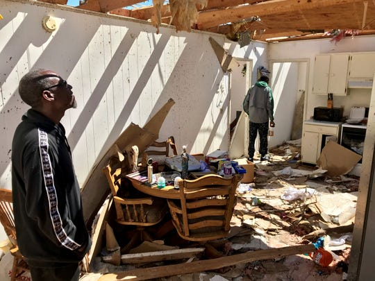 Raymond Sanders and his son Nijal Sanders, 18, walk through the wreckage of their home in Cairo, Georgia, on March 5, 2019, two days after it was nearly destroyed by a tornado.
