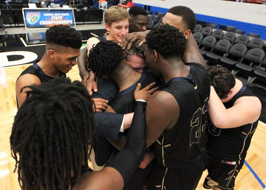 St. John Paul II coach Titus Nixon is mobbed by players as the Panthers' boys basketball team celebrates a 50-48 overtime victory against Orlando Christian Prep to capture a Class 3A state championship at the RP Funding Center in Lakeland on Tuesday.