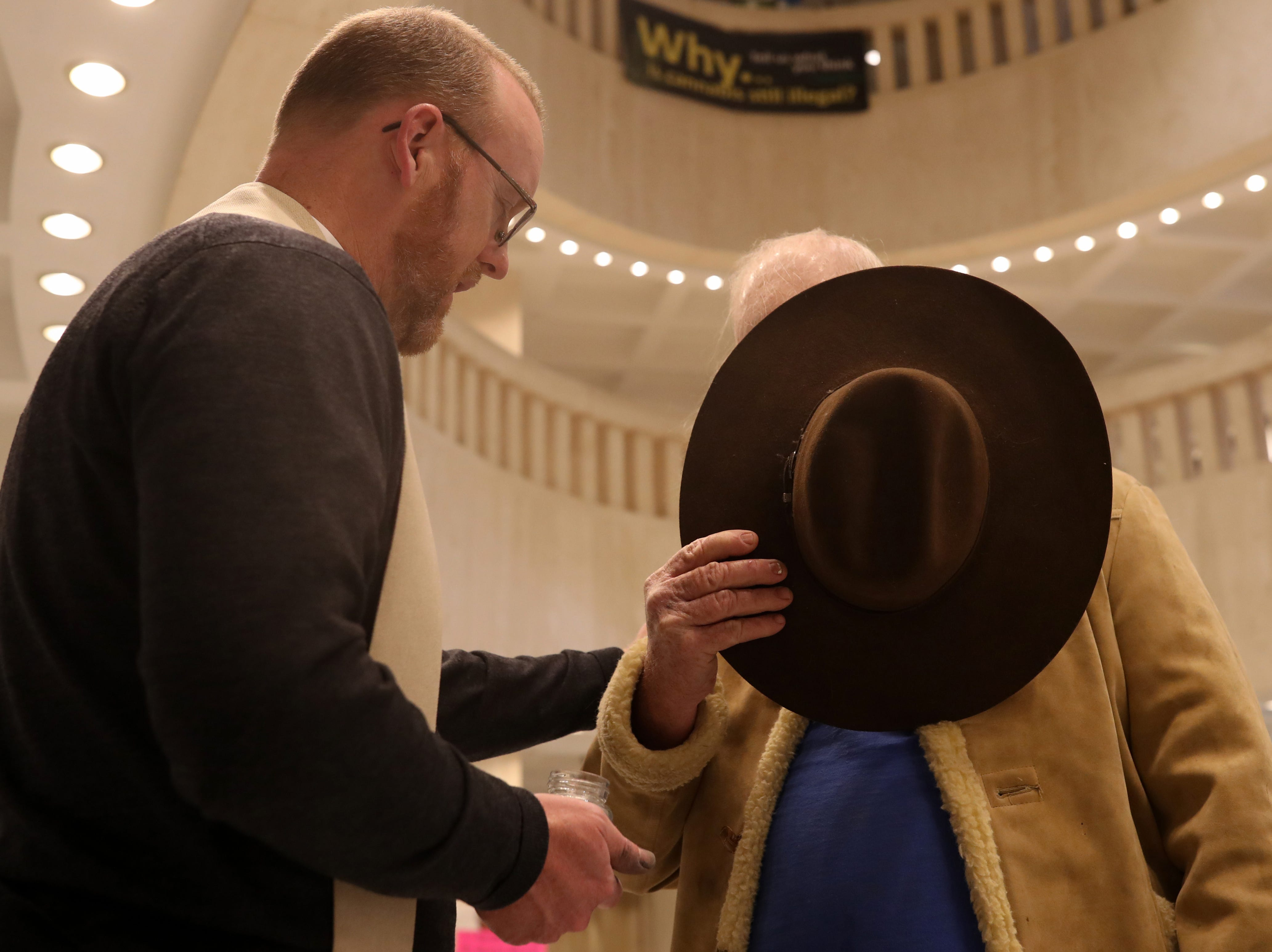 "Bruce Borders of Branford, Fla. removes his hat as he prays with Rev. David Killeen after receiving ashes from the St. John's Episcopal pastor who gave ""ashes to go"" in the Florida Capitol rotunda on Ash Wednesday, March 6, 2019."