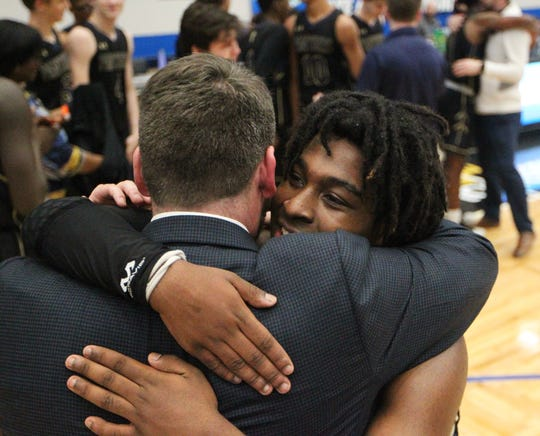 St. John Paul II's Tyreke McElwain gets a hug from coach Titus Nixon as the Panthers' boys basketball team celebrates a 50-48 overtime victory against Orlando Christian Prep to capture a Class 3A state championship at the RP Funding Center in Lakeland on Tuesday.