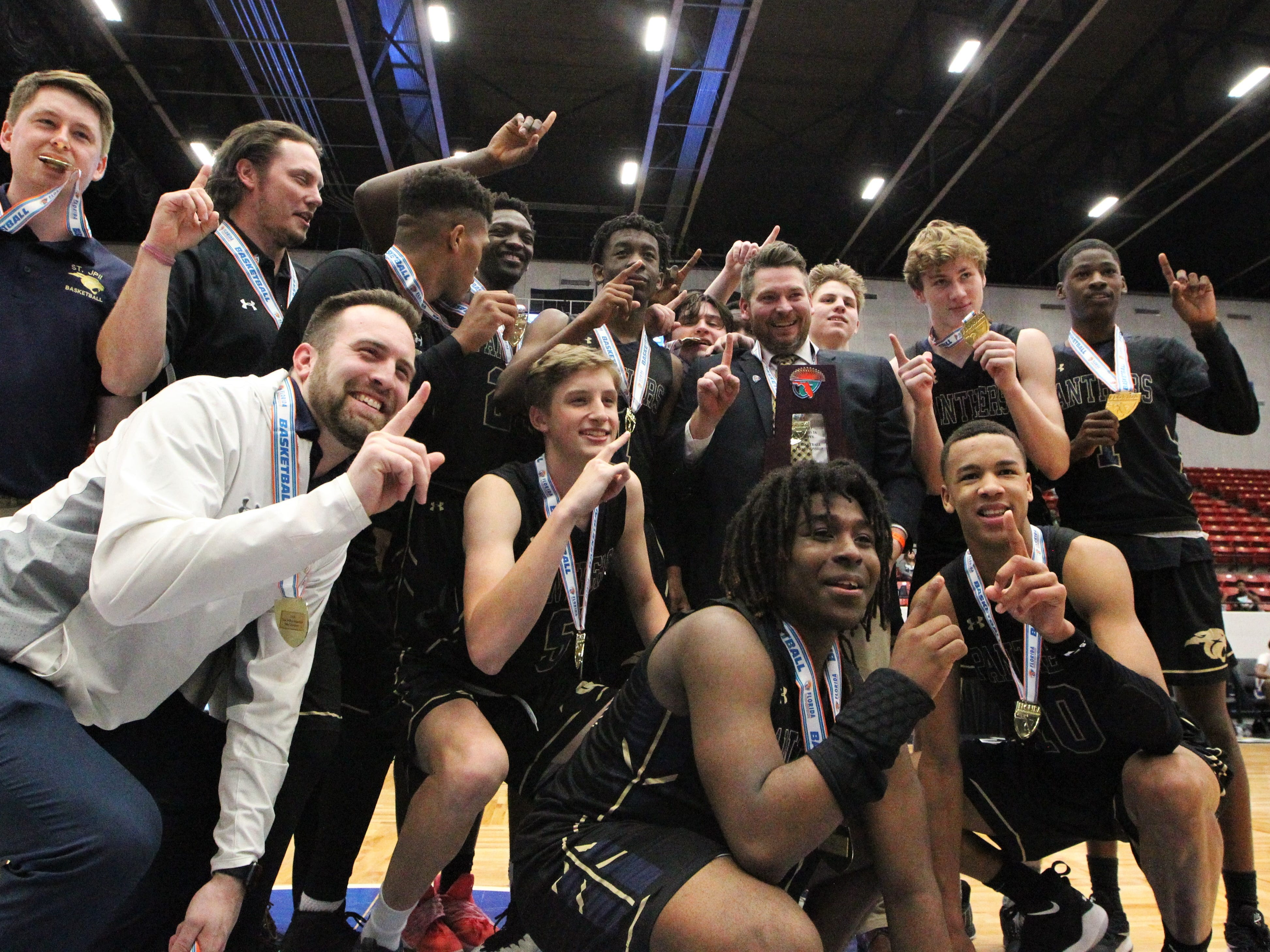 St. John Paul II's boys basketball team celebrates a 50-48 overtime victory against Orlando Christian Prep to capture a Class 3A state championship at the RP Funding Center in Lakeland on Tuesday.